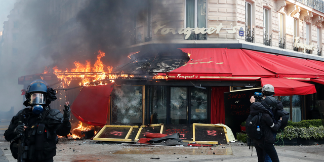 Paris famed restaurant Fouquet's burns on the Champs Elysees avenue during a yellow vests demonstration Saturday, March 16, 2019 in Paris. Paris police say more than 100 people have been arrested amid rioting in the French capital by yellow vest protesters and clashes with police. They set life-threatening fires, smashed up luxury stores and clashed with police firing tear gas and water cannon