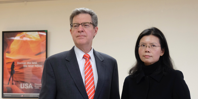 """Sam Brownback, U.S. ambassador-at-large for international religious freedom, left, stands with Lee Ching-yu, the wife of Taiwanese pro-democracy activist Lee Ming-che in Taipei, Taiwan, Tuesday, March 12, 2019. Describing China's internment of an estimated 1 million Muslims as a """"horrific situation,"""" a U.S. envoy on religion called Tuesday for an independent investigation into the detentions and for the release of those being held. (AP Photo/Johnson Lai)"""