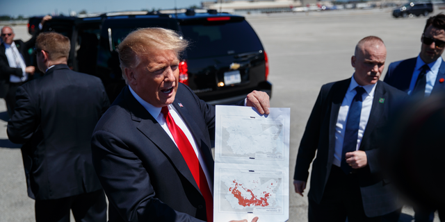 FILE - In this March 22, 2019, photo, President Donald Trump holds a a copy of two maps of Syria as he arrives on Air Force One, Friday, March 22, 2019, at Palm Beach International Airport, in West Palm Beach, Fla. There was just one problem when Trump walked down the stairs of Air Force One and unceremoniously declared that the Islamic State had lost the last of its territory in Syria. He wasn't supposed to announce it yet. (AP Photo/Carolyn Kaster)