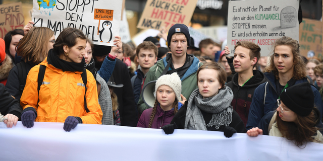 Swedish climate activist Greta Thunberg, front with white cap, attends a protest rally in Hamburg, Germany, on March 1, 2019. (Daniel Reinhardt/dpa via AP, file)
