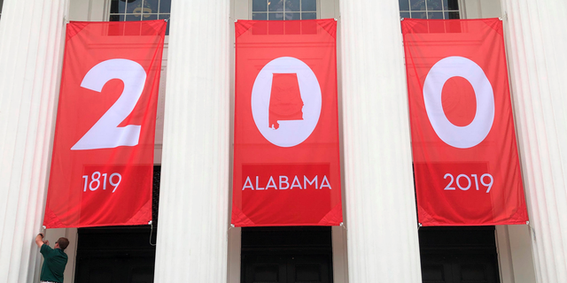 In this Feb. 28, 2019, photo a worker adjusts a banner celebrating Alabama's bicentennial outside the Department of Archives and History in Montgomery, Ala. Alabama is the latest state trying to balance a painful past with other parts of its history as it recognizes its 200th birthday as a state. (AP Photo/Jay Reeves)