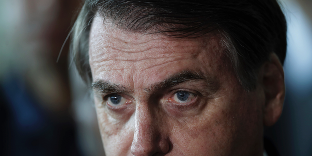 """Brazil's President Jair Bolsonaro listens to a reporter's question at the end of a military ceremony where he was awarded the Order of Military Judicial Merit, in Brasilia, Brazil, Thursday, March 28, 2019. Bolsonaro, a former army captain who waxes nostalgic for the 1964-1985 dictatorship, on Monday asked Brazil's Defense Ministry to organize """"due commemorations"""" to mark the upcoming March 31st anniversary of Brazil's 1964 military coup. (AP Photo/Eraldo Peres)"""
