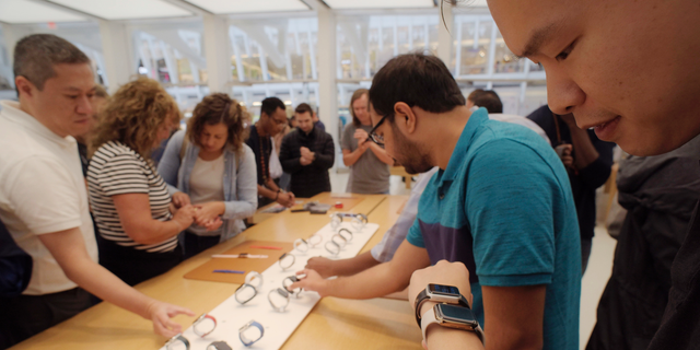 FILE- In this Sept. 21, 2018 file photo customers look at Apple Watches at an Apple store in New York. (AP Photo/Patrick Sison, File)