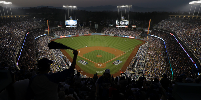 FILE - In this Oct. 27, 2018, file photo, fans cheer from the top of Dodger Stadium during Game 4 of the World Series baseball game between the Boston Red Sox and Los Angeles Dodgers in Los Angeles. Los Angeles police say a 47-year-old man was hospitalized after an argument turned violent outside Dodger Stadium. Police say the man was punched once by another man and fell to the ground in a parking lot following the six-hour game Friday night against the Arizona Diamondbacks. (AP Photo/Elise Amendola, File)