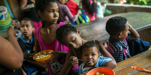 Eight-year-old Franyelis feeds her baby brother Joneiber as their mother Francibel Contreras holds a bowl of scrambled eggs and rice, at a soup kitchen in the Petare slum, Caracas, Venezuela. Contreras brings her three malnourished children to the soup kitchen in the dangerous hillside slum where they scoop in spoonfuls of food in what could be their only meal of the day. (AP Photo/Rodrigo Abd)