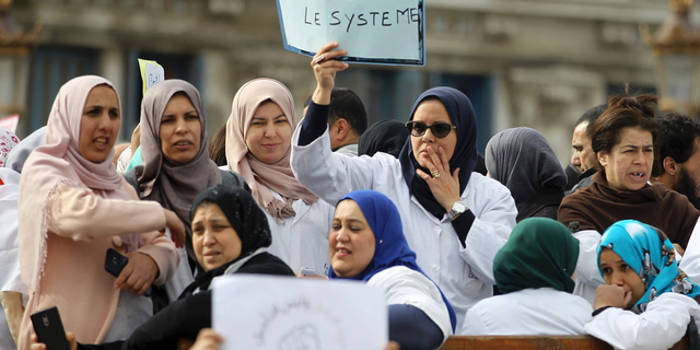 An Algerian woman holds a placard that reads, 'we need to disinfect the system' during a protest in Algiers, Algeria, Tuesday, March 19, 2019. (AP Photo/Anis Belghoul)