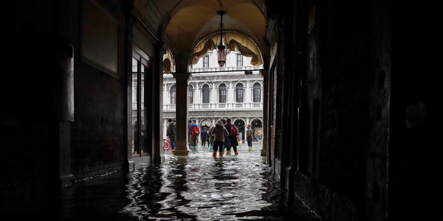 FILE - In this Thursday, Nov. 1, 2018 file photo, tourists walk in the flooded St. Mark's Square in Venice, Italy, as rainstorms and strong winds hit the area. On Thursday, March 28, 2019, the United Nations' weather agency says extreme weather in 2018 hit 62 million people worldwide last year and created 2 million refugees as man-made climate change worsened. (AP Photo/Luca Bruno)