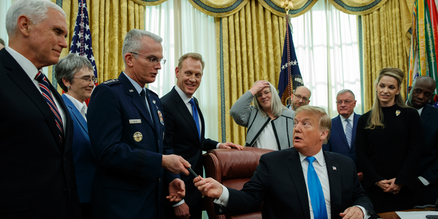 """President Donald Trump hands a pen to Air Force Gen. Paul Selva after signing """"Space Policy Directive 4"""" in the Oval Office of the White House, Tuesday, Feb. 19, 2019, in Washington. (AP Photo/ Evan Vucci)"""