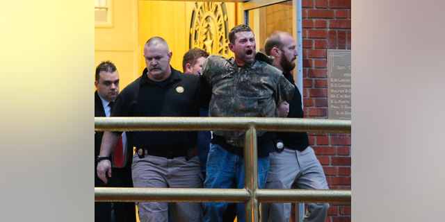 In this Thursday, Feb. 28, 2019 photo, Gordon Coble, center, is led out of the of the Texas State Penitentiary in Huntsville, Texas, after reacting to the execution of his father, Billie Wayne Coble.  Chaos erupted outside Texas' death chamber Thursday night when the son of the condemned inmate pounded on the chamber windows, shouted obscenities and threw fists after his father spoke his final words. (Jerry Larson/Waco Tribune-Herald via AP)