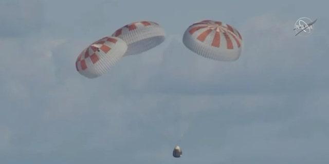 Crew Dragon deployed its four main parachutes before splashing down in the Atlantic Ocean. (NASA TV)