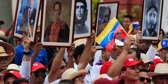 Cuban doctors hold up framed pictures (L-R) of late President Hugo Chavez, Venezuela's National hero Simon Bolivar, Ernesto 'Che' Guevara, Cuban national hero Jose Marti and Fidel Castro during a march of farmers in support of Venezuela's President Nicolas Maduro in Caracas February 26, 2014. REUTERS/Tomas Bravo