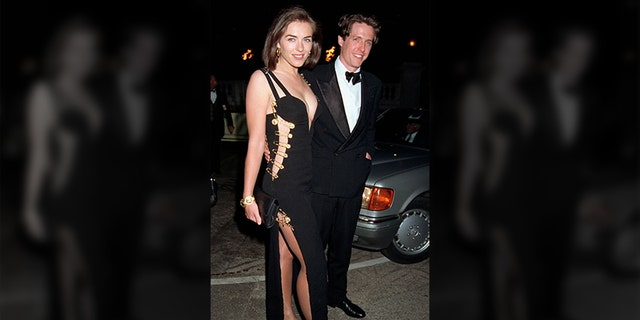 Elizabeth Hurley, pictured with Hugh Grant, wears a Versace dress to the premiere of 'Four', in her tiny one-bedroom apartment, she recalled. Wedding and A Funeral 'held in Leicester Square on March 09, 1994 in London, England.