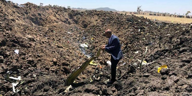 In this photo taken from the Ethiopian Airlines Facebook page, the CEO of Ethiopian Airlines, Tewolde Gebremariam, looks at the wreckage of the plane that crashed shortly after takeoff from Addis Ababa, Ethiopia, Sunday March 10, 2019.