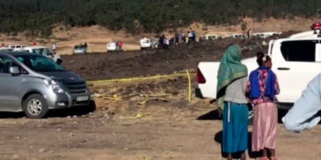 In this image taken from video, people stand around the crash site of an Ethiopian Airlines flight that crashed shortly after takeoff lies at the scene at Hejere near Bishoftu, or Debre Zeit, some 31 miles south of Addis Ababa, in Ethiopia Sunday, March 10, 2019.