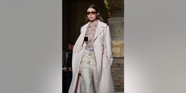 Gigi dons a sheer top and light pink coat