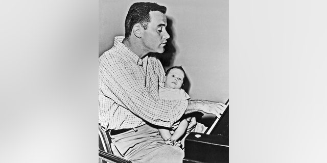 "Little Christopher Lemmon is wide-eyed at the playing of his father, actor Jack Lemmon. Lemmon was taking time out from the filming of the movie ""Phffft"" to hold two-and-a-half-month-old Chris for his camera debut. — Getty"
