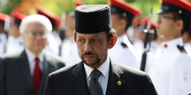 Sultan of Brunei Hassanal Bolkiah walks back after inspecting the guard of honor, accompanied by Singapore President, Tony Tan Keng Yam during the welcome ceremony at the Istana on July 5, 2017 in Singapore.