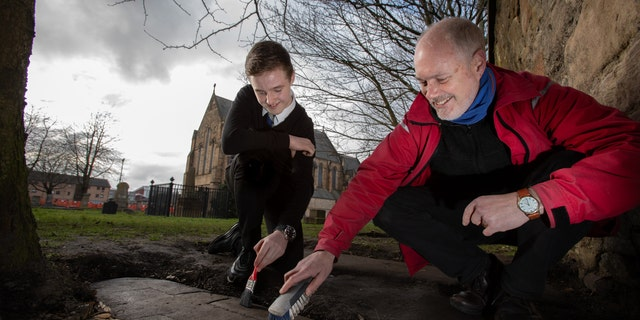 Mark McGettigan and Professor Stephen Driscoll of the University of Glasgow examine one of the rediscovered stones at Govan Old Parish Church.