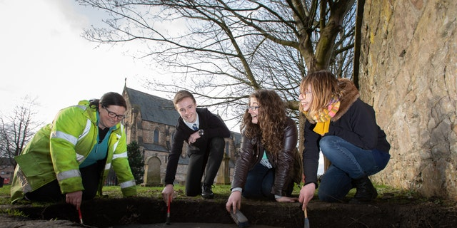 "(Left to right) Nicola Reid, field archaeolgist, Northlight Heritage; Mark McGettigan; Megan Kasten, project office and volunteer, Northlight Heritage and Ingrid Shearer, community engagement officer for ""Stones & Bones"" excavation, Northlight Heritage examining one of the three Govan Stones rediscovered at Govan Old Parish Church."