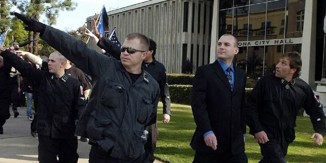 Jeff Schoep, second right in business suit, commander of the National Socialist Movement, under police protection after a rally against illegal immigration in Pomona, Calif. (Thomas R. Cordova/The Orange County Register via AP)