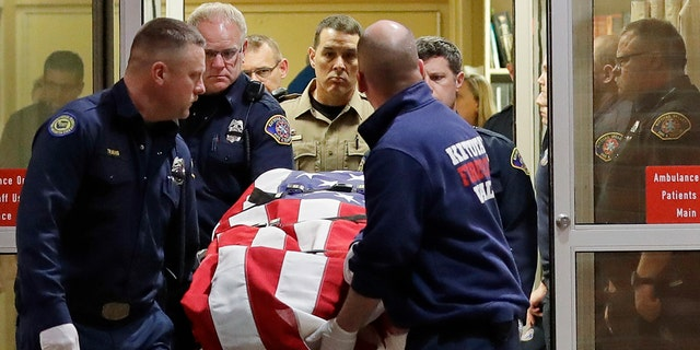 The body of a Kittitas County sheriff's deputy is draped with a U.S. flag as it is carried out of Kittitas Valley Healthcare Hospital in the early morning hours of Wednesday, March 20, 2019, in Ellensburg, Wash. (Associated Press)