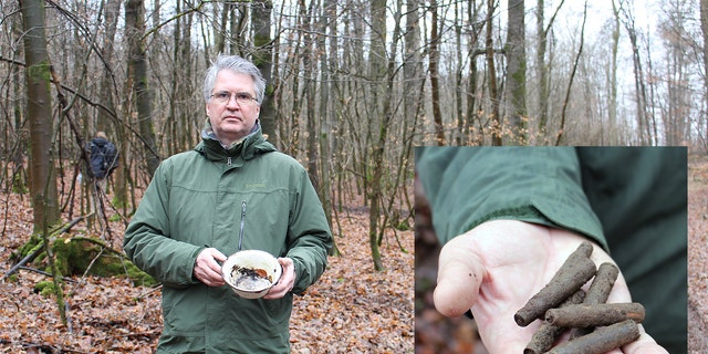 Cartridge cases and an enamel bowl found at one of the massacre sites are shown by Dr.Marcus Weidner, a historian at the LWL Institute for Westphalian Regional History.