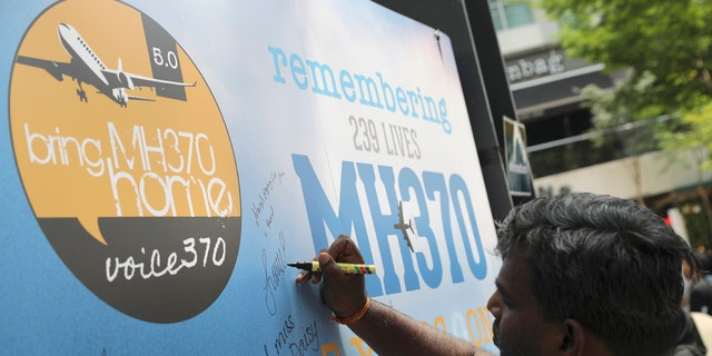 A man writes a condolence message during a Day of Remembrance for MH370 event in Kuala Lumpur, Malaysia, Sunday, March 3, 2019.