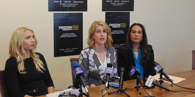 Bethany Mendez, center, along with attorney Harmeet K. Dhillon, right and Mariah Gondeiro-Watt, litigation counsel for the Freedom Foundation, at a press conference on Monday.