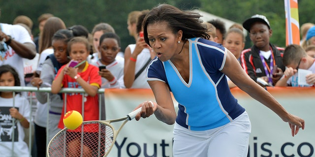 """US First Lady Michelle Obama plays tennis during """"Let's Move-London"""" event at the Winfield House in London on July 27, 2012, hours before the start of the London 2012 Olympic Games."""
