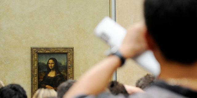 A tourist takes souvenir photos of Italian painter Leonardo da Vinci's famed portrait Mona Lisa at the Louvre Museum in Paris, Aug. 12, 2009.