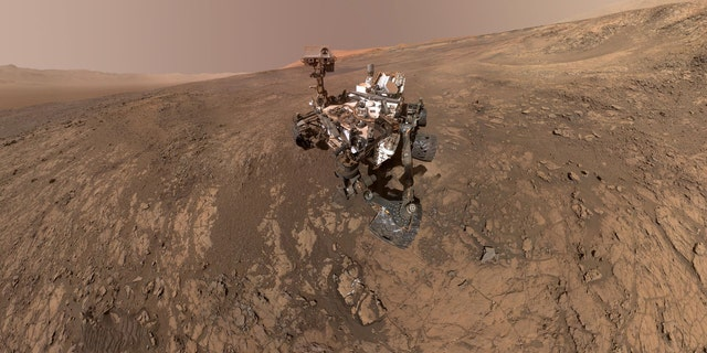 This self-portrait of NASA's Curiosity Mars rover shows the vehicle on Vera Rubin Ridge in Gale crater on Mars. North is on the left and west is on the right, with Gale crater's rim on the horizon of both edges. This mosaic was assembled from dozens of images taken by Curiosity's Mars Hands Lens Imager (MAHLI). They were all taken on Jan. 23, 2018, during Sol 1943. (Credit: NASA/JPL-Caltech/MSSS)