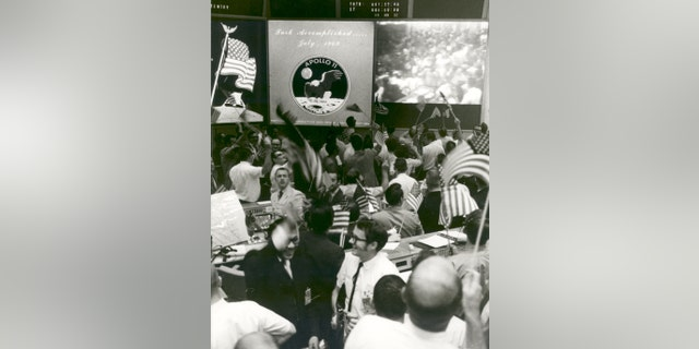 Flight controllers at Mission Control applaud the splashdown and success of the Apollo 11 lunar mission on July 24, 1969. (NASA)