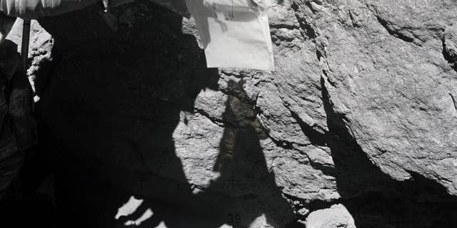 Duke examines the surface of a large lunar boulder during the Apollo 16 mission. (NASA)