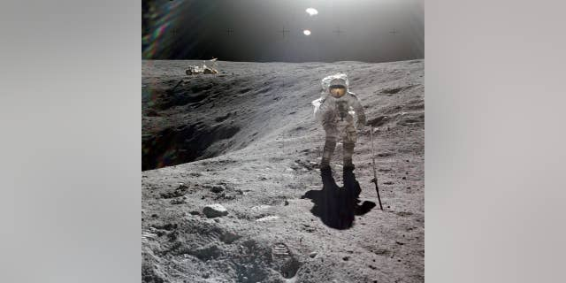 Astronaut Charles Duke, Apollo 16 lunar module pilot, is photographed collecting lunar samples at Station No. 1 at the Descartes landing site.