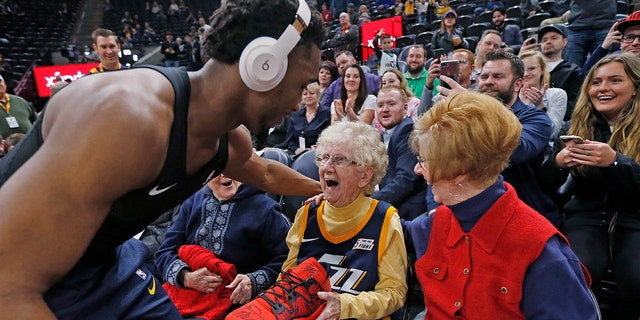 Utah Jazz guard Donovan Mitchell, left, hands his basketball shoe to Roberta Morgan, 102, after he warmed up for the team's NBA basketball game against the Milwaukee Bucks on Saturday, March 2, 2019, in Salt Lake City.