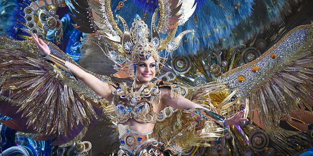 TOPSHOT - A nominee for queen performs during the main stage of the Carnival of Santa Cruz in Santa Cruz de Tenerife on the Spanish Canary island of Tenerife, on February 07, 2018. The costumes are more than five meters high and over 80 kilos in weight. The event began on January 12 and finishes on February 18 with orchestras playing Caribbean and Brazilian rhythms throughout the festivities that range from elections for the Carnival Queen, the Junior Queen and the Senior Queen, to children and adult murgas (satirical street bands), comparsas (dance groups) and street performances. / AFP PHOTO / DESIREE MARTIN (Photo credit should read DESIREE MARTIN/AFP/Getty Images)