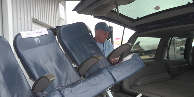 Volunteers load a set of airplane seats into a shopper's trunk at the Delta Surplus Sale.