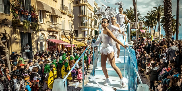 Revelers in their colorful costumes dance on their float during the children carnival parade in Sitges. (Photo by Matthias Oesterle/Corbis via Getty Images)