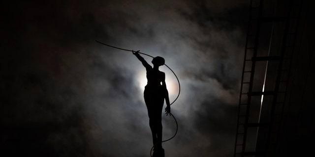 A sculpture is silhouetted against a full moon in Brussels, Wednesday, March 20, 2019. (AP Photo/Francisco Seco)
