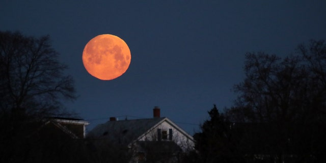 The moon sets over the Dorchester neighborhood of Boston on the early morning of March 20, 2019.