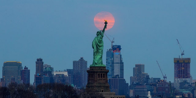 The last supermoon of 2019 rises behind the Statue of Liberty in New York, United States on March 20, 2019.