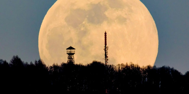 A lookout tower, left, and the broadcast tower of Antenna Hungaria at the top of Karancs mountain are backdropped by the rising moon as seen from the vicinity of Karancskeszi village, 128 kms northeast of Budapest, Hungary, Wednesday, March 20, 2019.