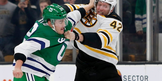 Carolina Hurricanes left wing Micheal Ferland and Boston Bruins right wing David Backes fight during the first period of an NHL hockey game, on Tuesday, March 5, 2019.