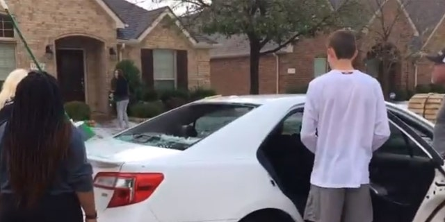 Residents in Frisco work to scoop hail out of the back of a car after windows were shattered during a hailstorm on Sunday.