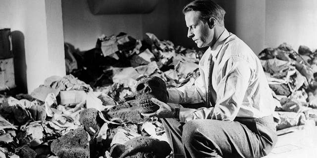 Norwegian anthropologist and explorer Thor Heyerdahl photographed with archaeological artifacts from Easter Island, 1957.