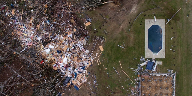 Debris from a home litters a yard the day after a tornado blew it off its foundation, lower right, in Beauregard, Ala., Monday, March 4, 2019.