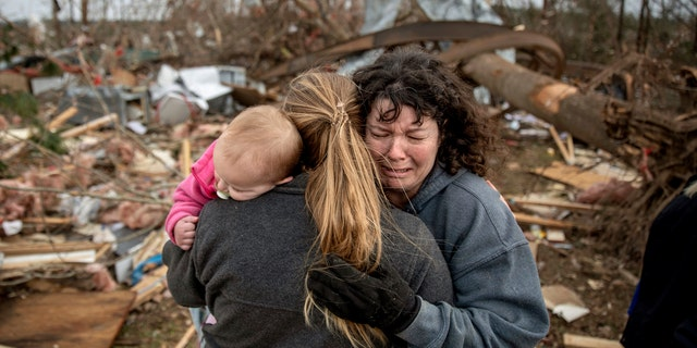 Carol Dean, right, cries while embraced by Megan Anderson and her 18-month-old daughter Madilyn, as Dean sifts through the debris of the home she shared with her husband, David Wayne Dean, who died when a tornado destroyed the house in Beauregard, Ala., Monday, March 4, 2019.