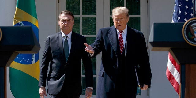 President Donald Trump and Brazilian President Jair Bolsonaro arrive for a news conference in the Rose Garden of the White House, Tuesday, March 19, 2019, in Washington. (AP Photo/Evan Vucci)