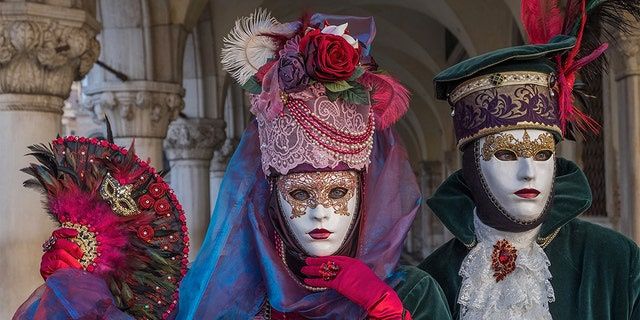 VENICE, ITALY - FEBRUARY 04: People wearing carnival costumes pose in St. Mark square during the Flight of Angel on February 4, 2018 in Venice, Italy. The theme for the 2018 edition of Venice Carnival is 'Playing' and will run from 27 January to 13 February. (Photo by Awakening/Getty Images)