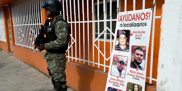 A Civil Forces police officer stands next to a banner with pictures of five youngsters who went missing January 11, 2016, in Tierra Blanca community, Veracruz State, Mexico.